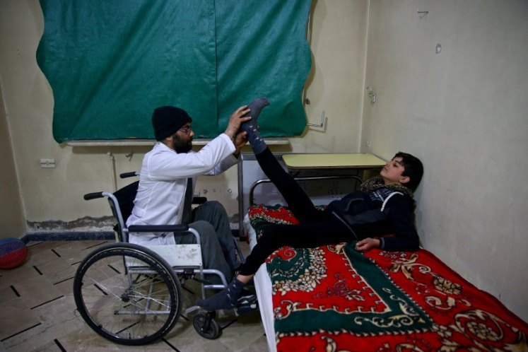 The Wider Image: In Syria makeshift centre treats the paralysed